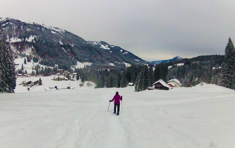 zasněžená příroda, plno sněhu, žena jde s hůlkami sněhem k chatkám, kolem jsou lesy